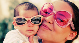Mama and Baby wearing sunglasses, hugging, and looking joyful.